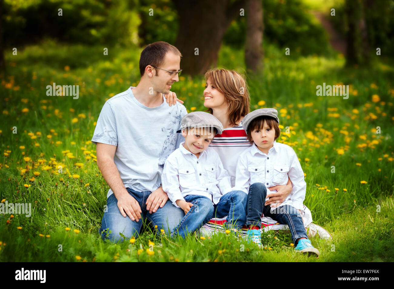 Family of four, mother, father and two boys, parent looking at each other, laughing, smiling, hugging, giving a - Stock Image