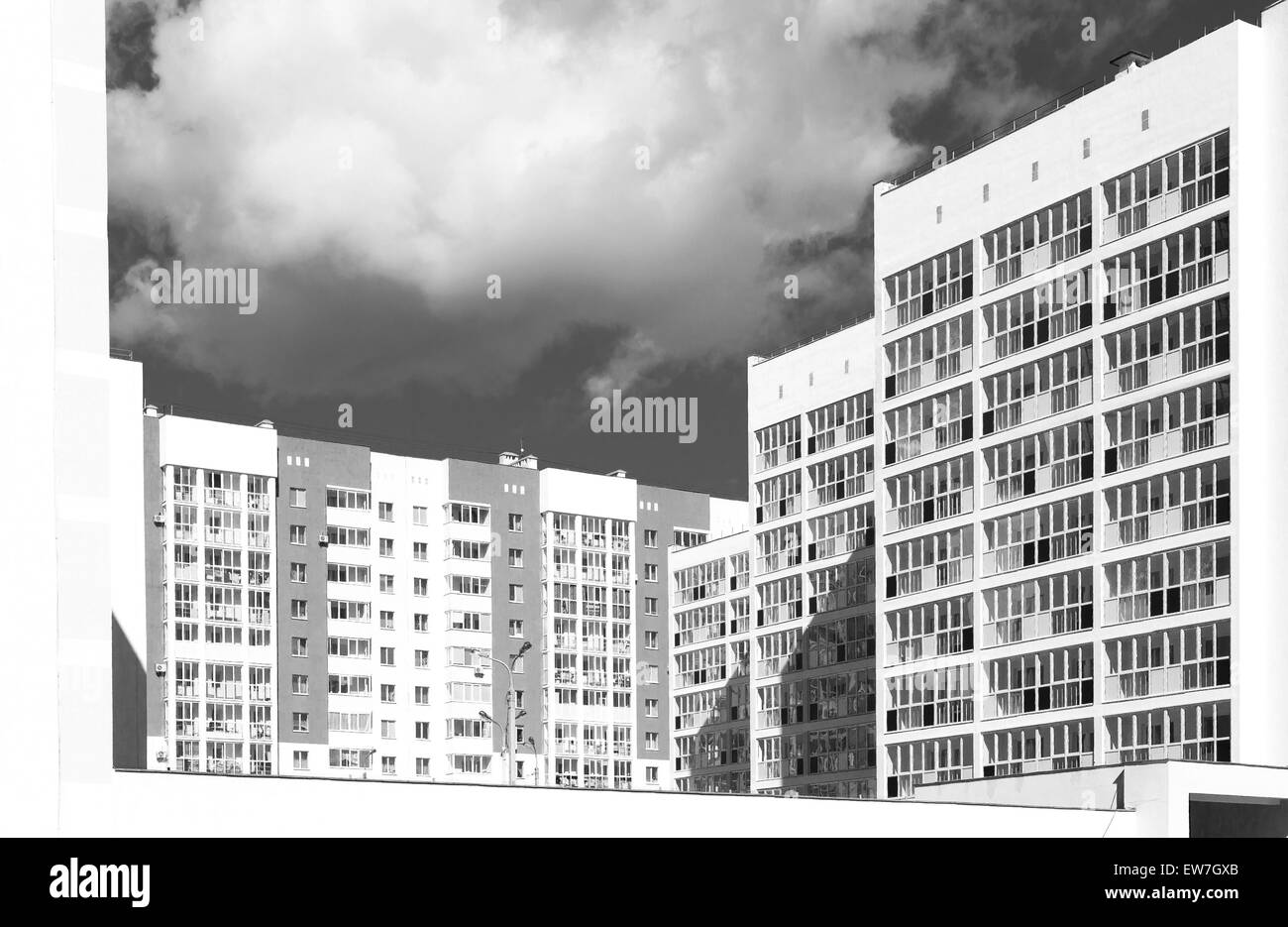 Monochrome style modern public housing apartment buildings with shadow area and dark sky - Stock Image