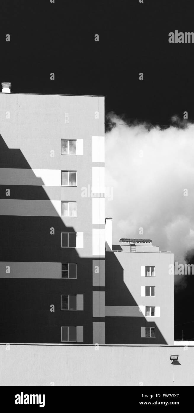 Monochrome style modern housing apartments with shadow area and dark sky - Stock Image