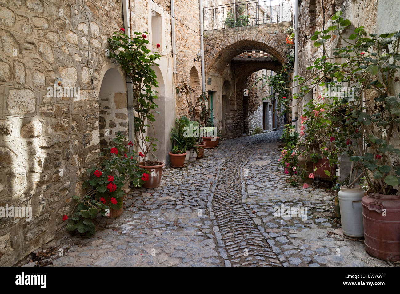 Small alley with bows and flowers in the medieval village of Mesta, on the isle of Chios, Greece - Stock Image