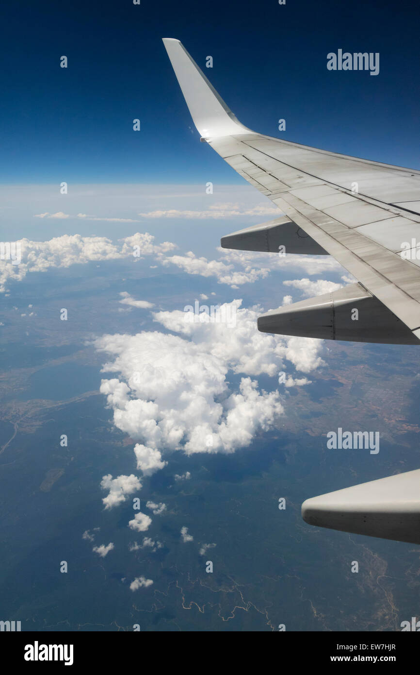 Wing of an aeroplane above the clouds in the sky - Stock Image