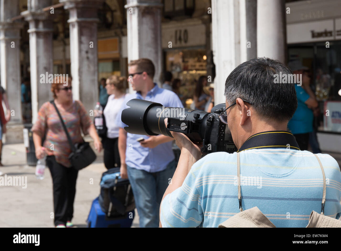 Tourist taking a photograpgh in St Mark's Square Venice Italy - Stock Image