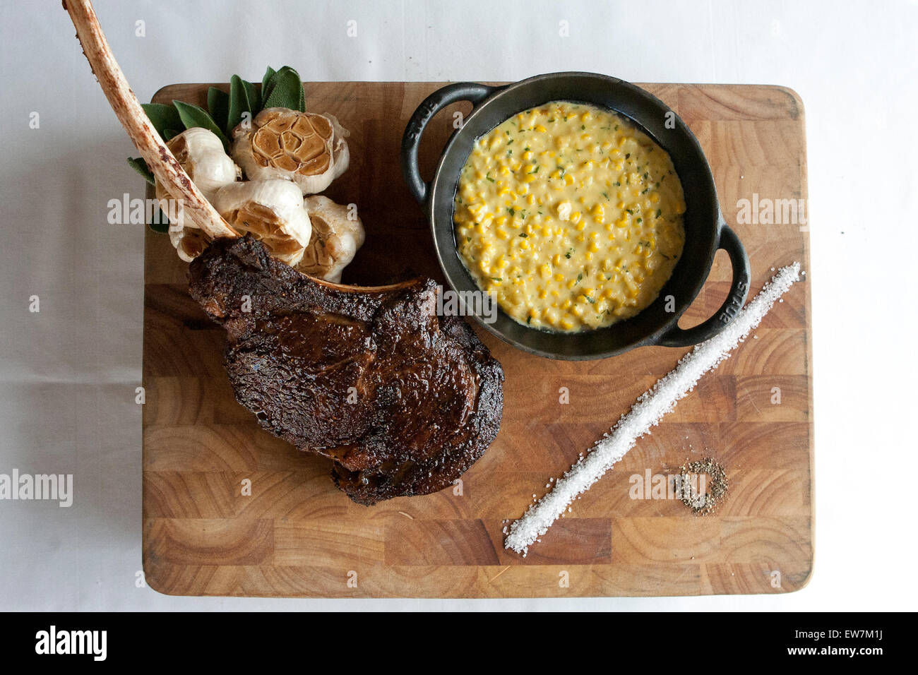 Steak dinner with garlic and corn - Stock Image