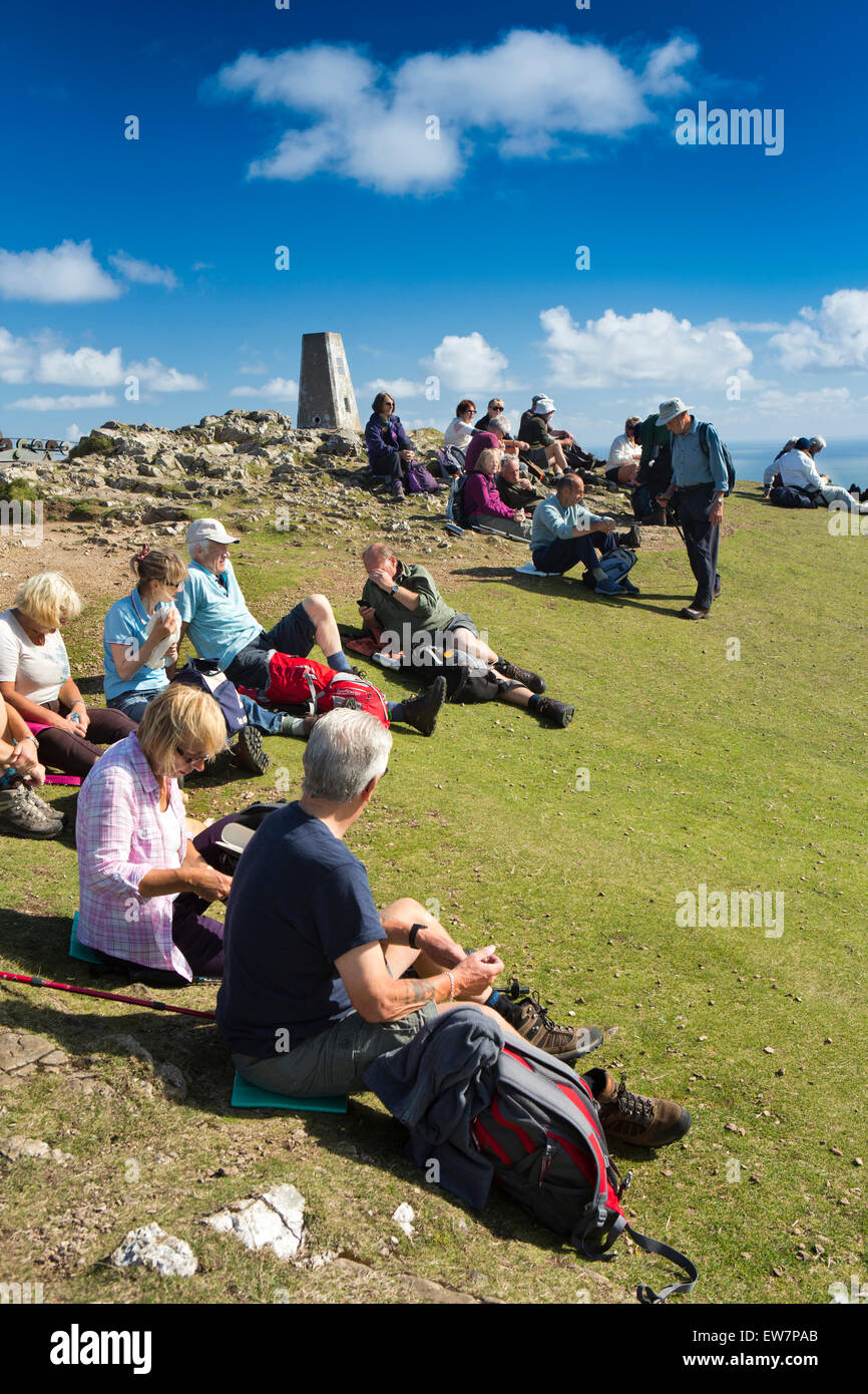 UK, Wales, Conwy, Llandudno, Great Orme Summit, group of walkers resting at trig point - Stock Image