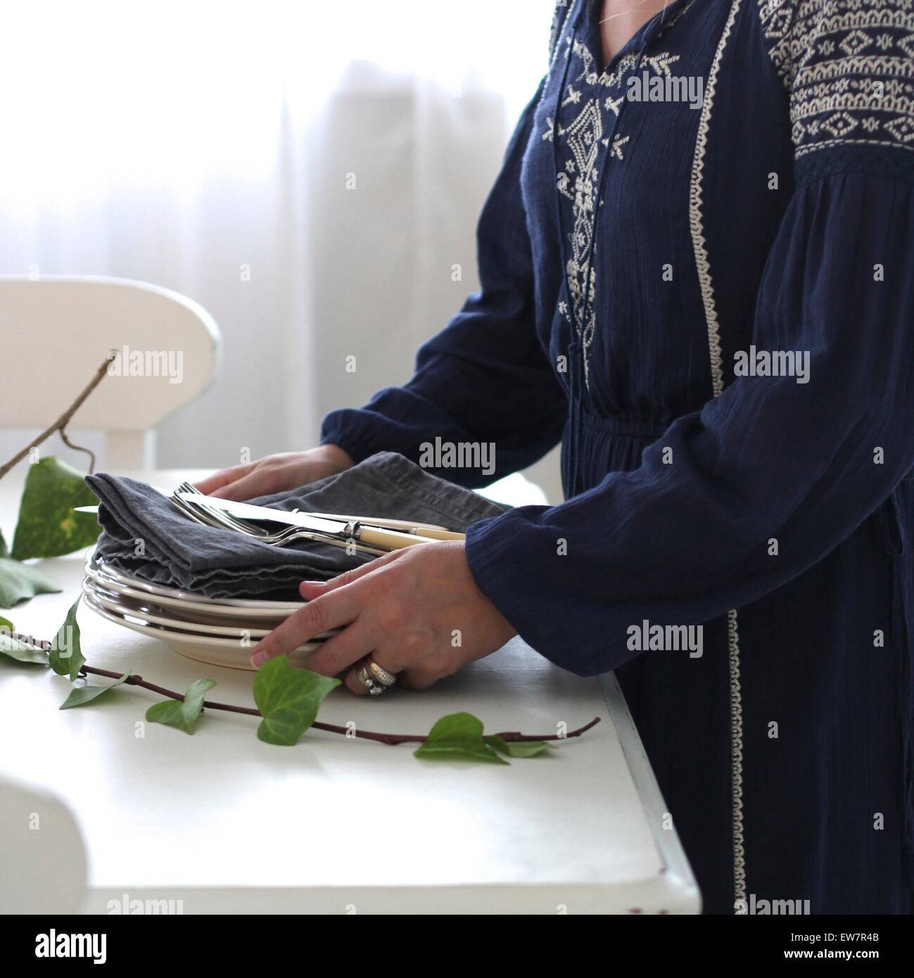 Side view of a woman laying table for dinner - Stock Image