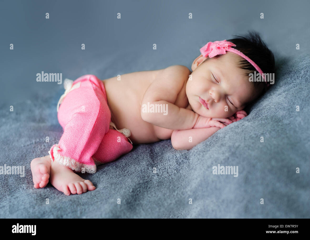 Baby girl smiling in her sleep - Stock Image
