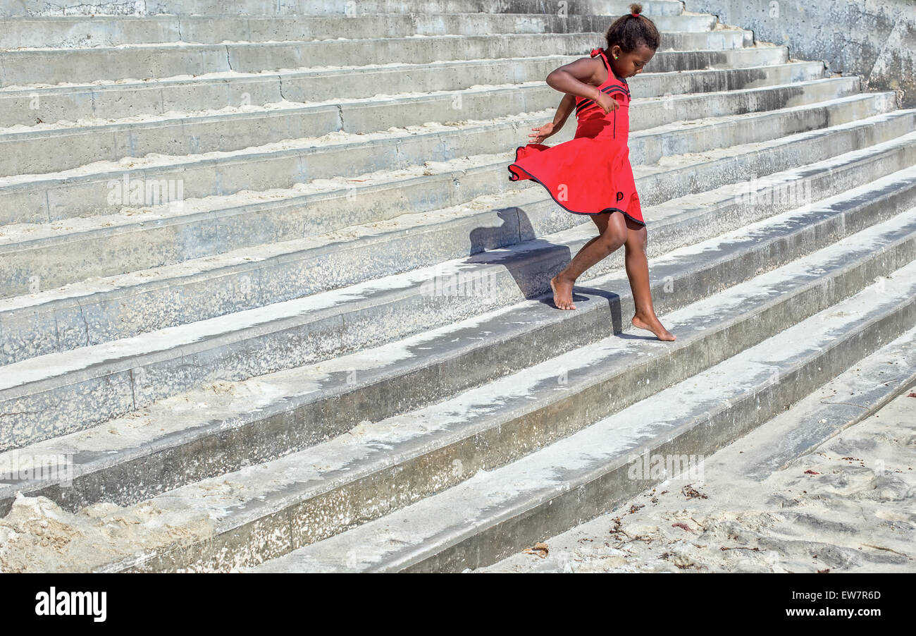 Girl in a red dress running down steps Stock Photo