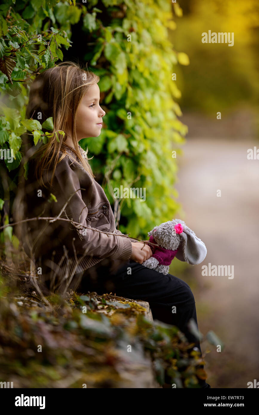 Side view of  a girl holding a stuffed bunny toy - Stock Image