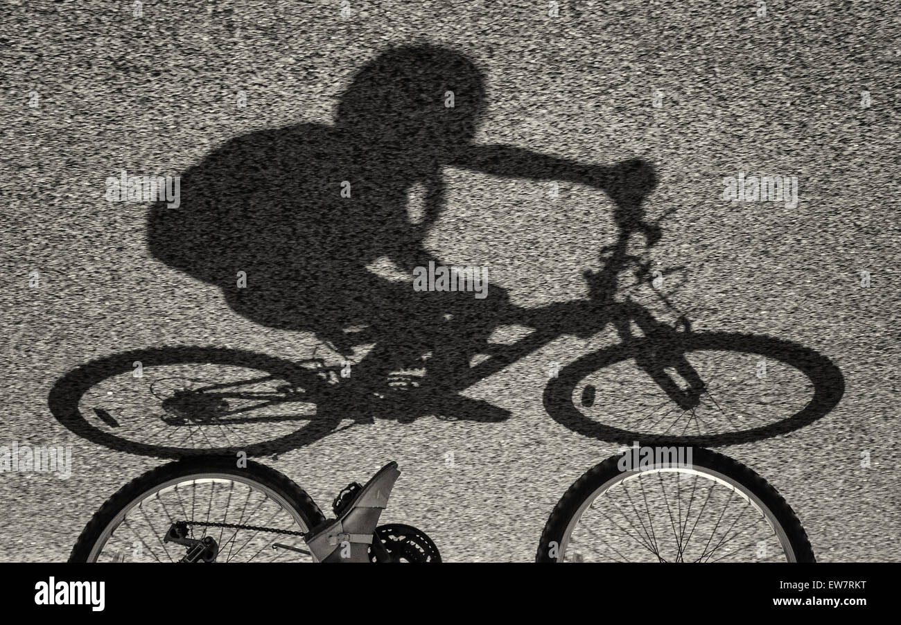 Shadow of a girl riding a bike - Stock Image