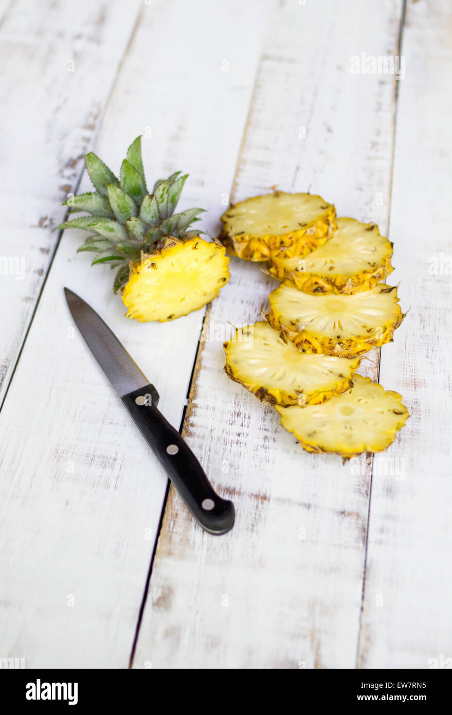 Still life of a pineapple sliced into pieces with a knife on a wooden table - Stock Image