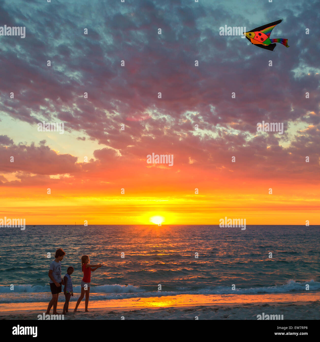 Three children flying a kite on beach at sunset, Hillarys, Joondalup, Australia - Stock Image