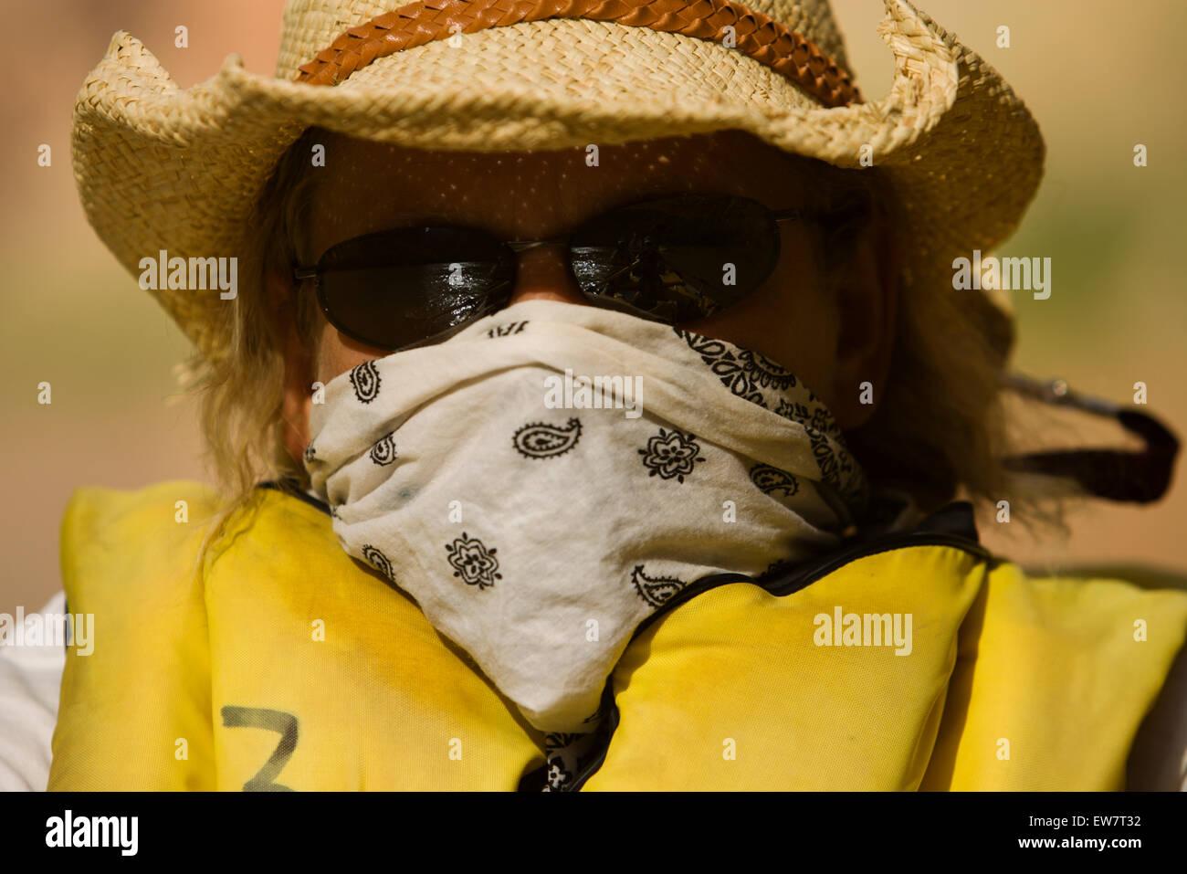 Headshot of a woman wearing a lifejacket, sunglass and staw hat. - Stock Image