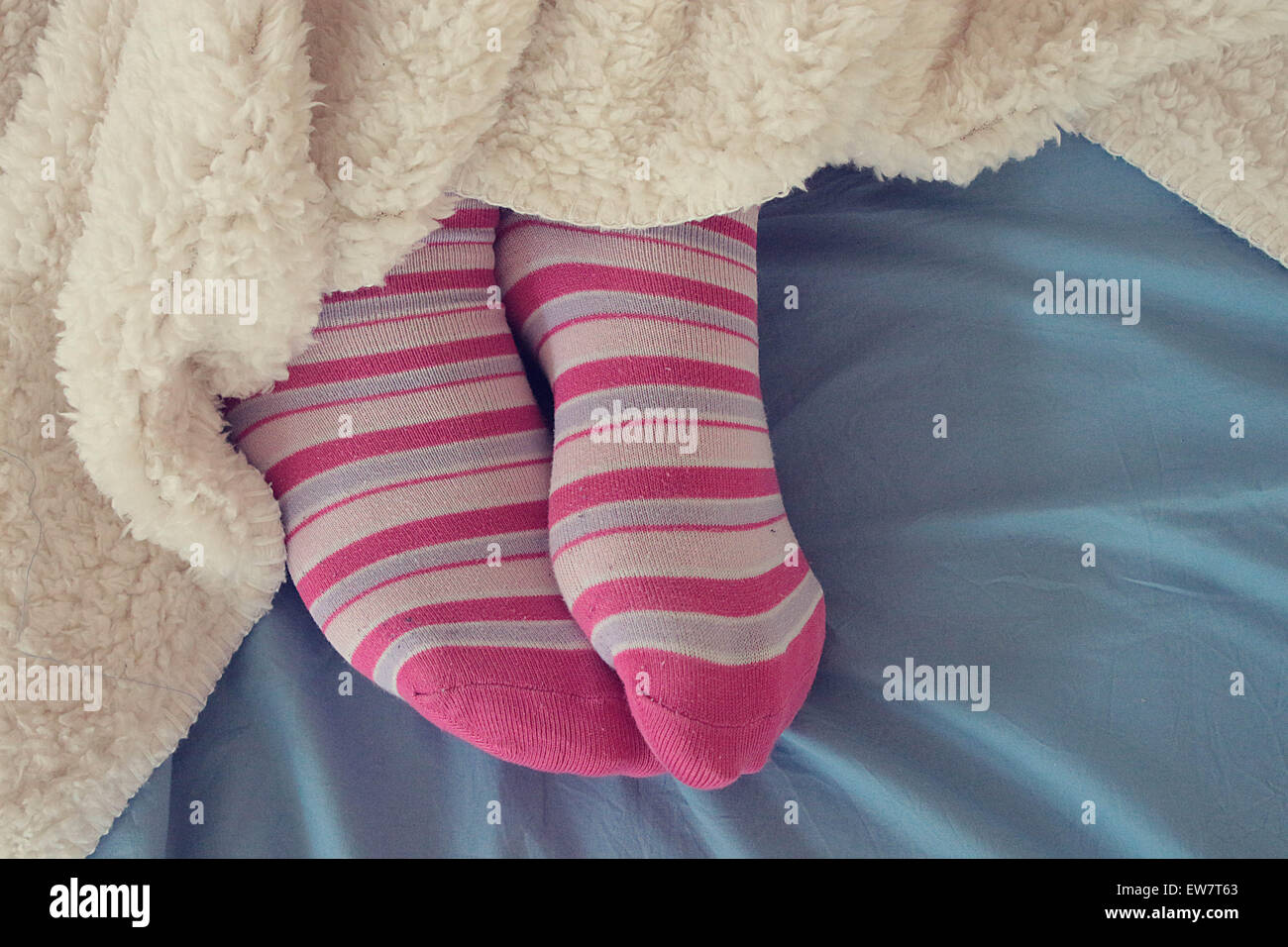 Woman's feet in pink socks sticking out from under a blanket - Stock Image