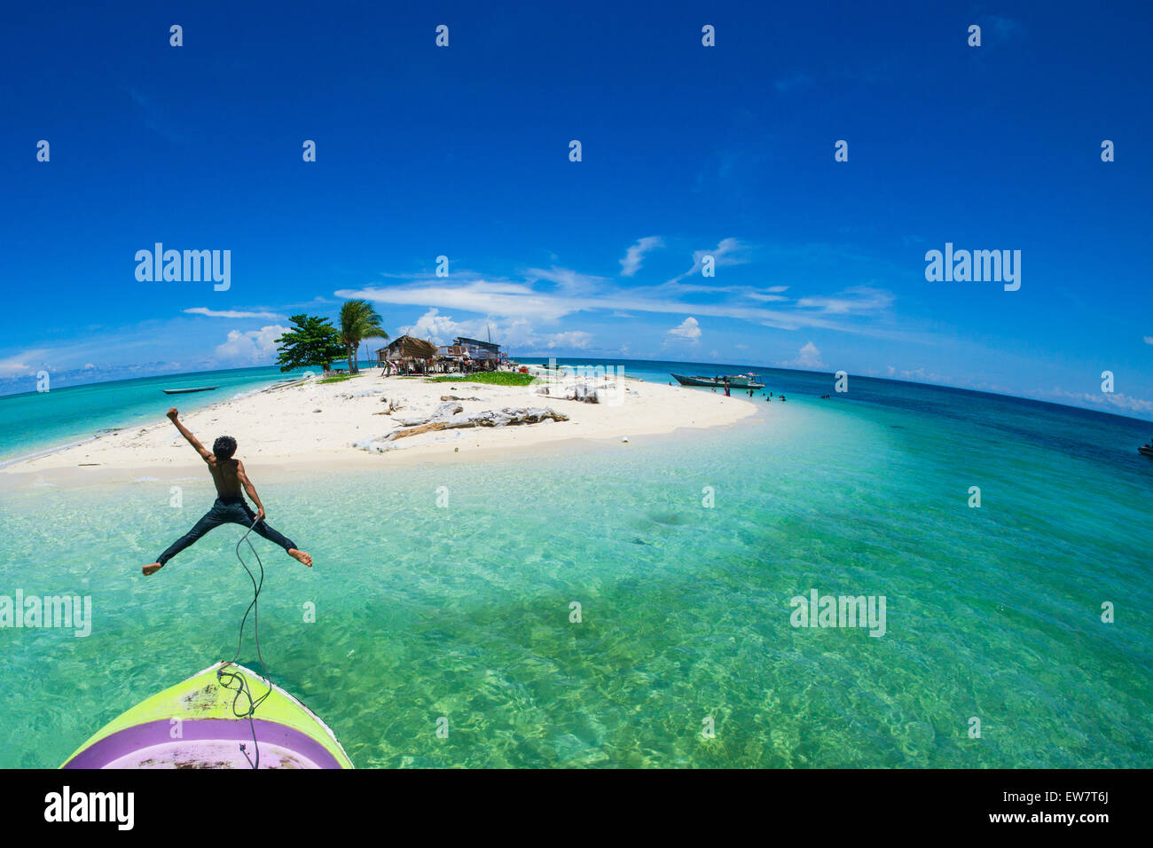 Teenage boy jumping off the front of a boat into the sea, Semporna, Sabah, Malaysia - Stock Image