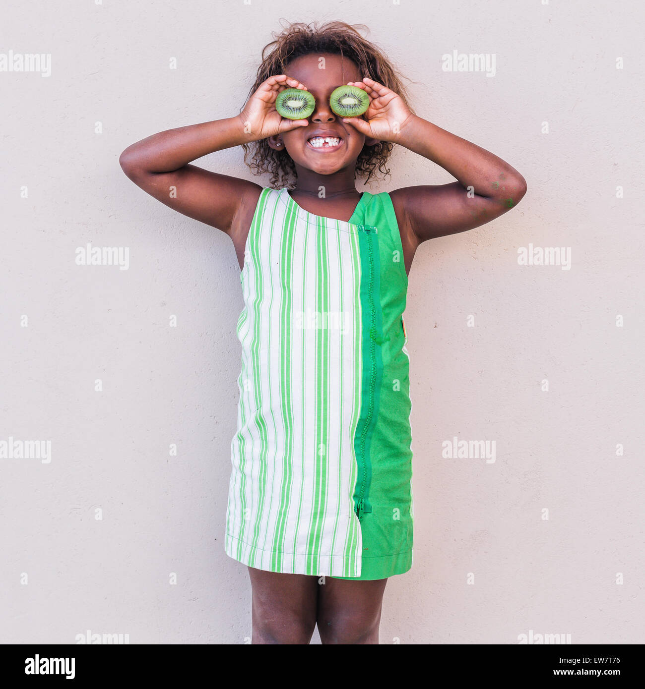 Smiling girl in green dress holding kiwi fruit in front of her eyes - Stock Image