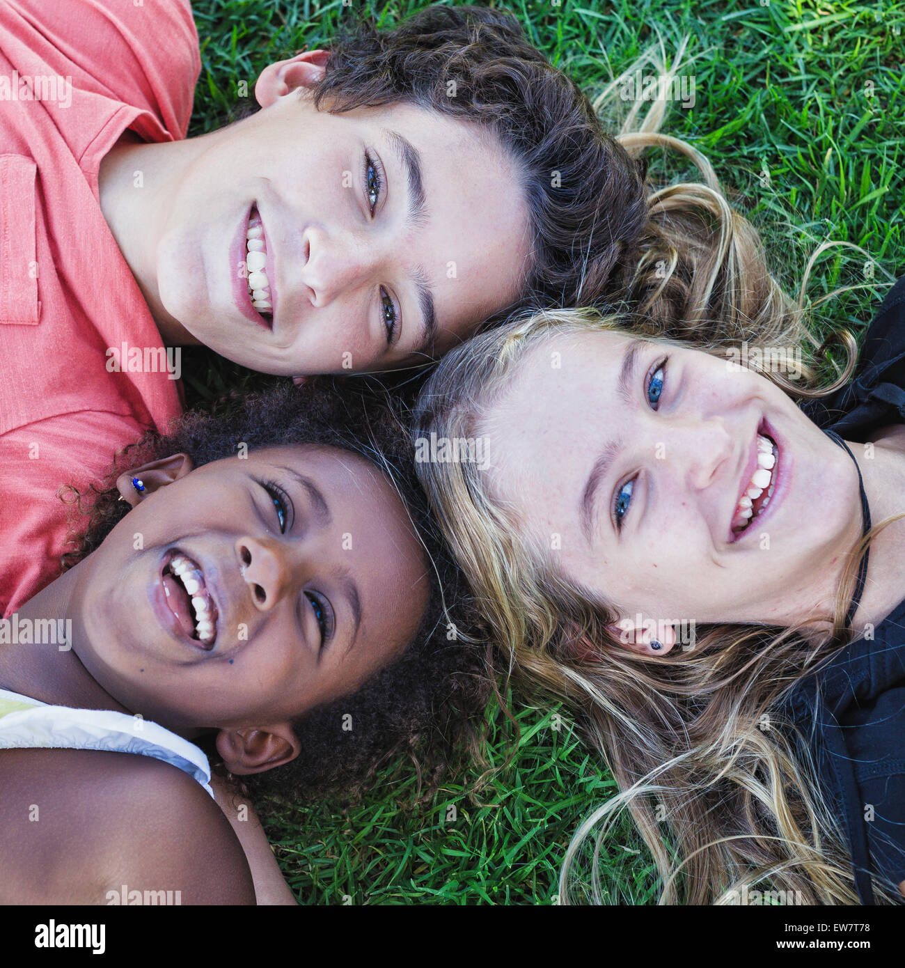 Elevated view of three smiling children lying on the grass - Stock Image