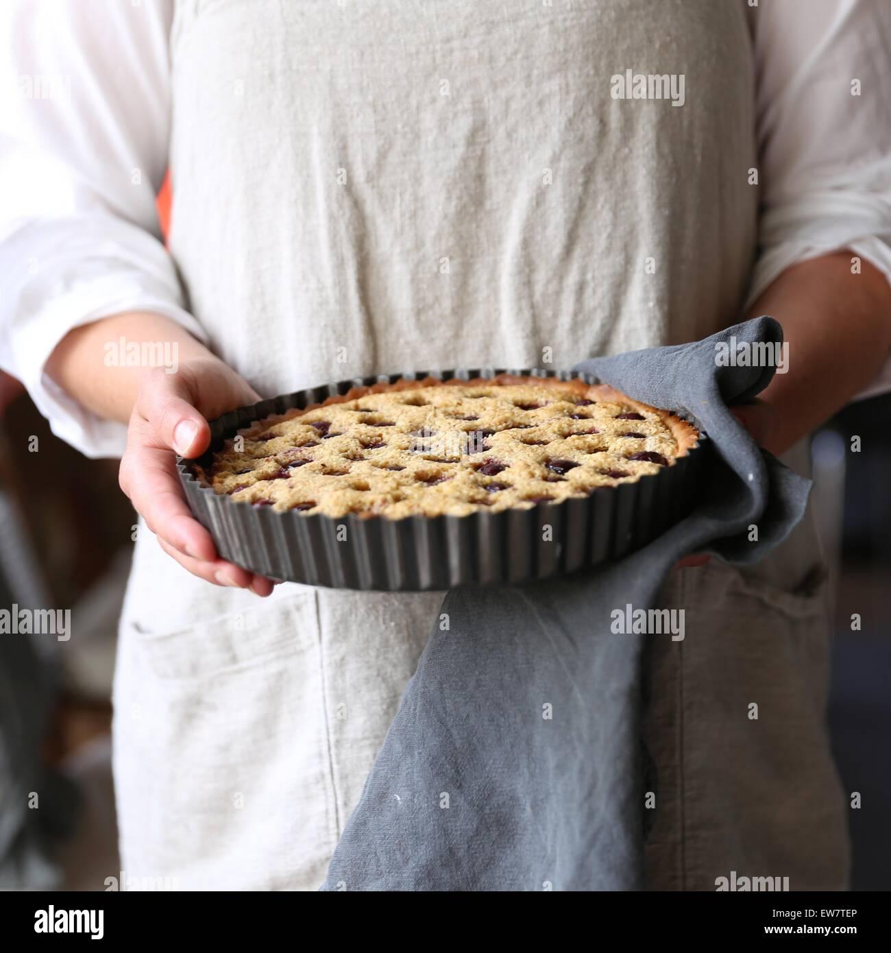 Woman holding freshly baked fruit pie - Stock Image