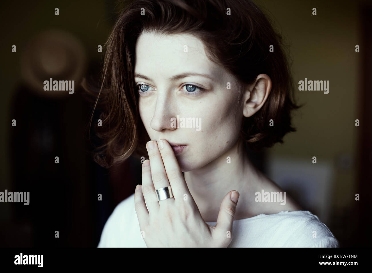Portrait of a woman holding her hand to her mouth - Stock Image