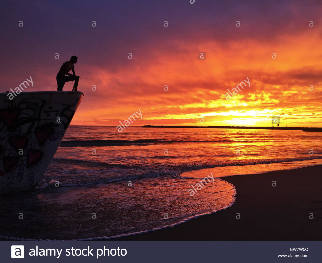 Silhouette of a man standing on a boat wreck - Stock Image