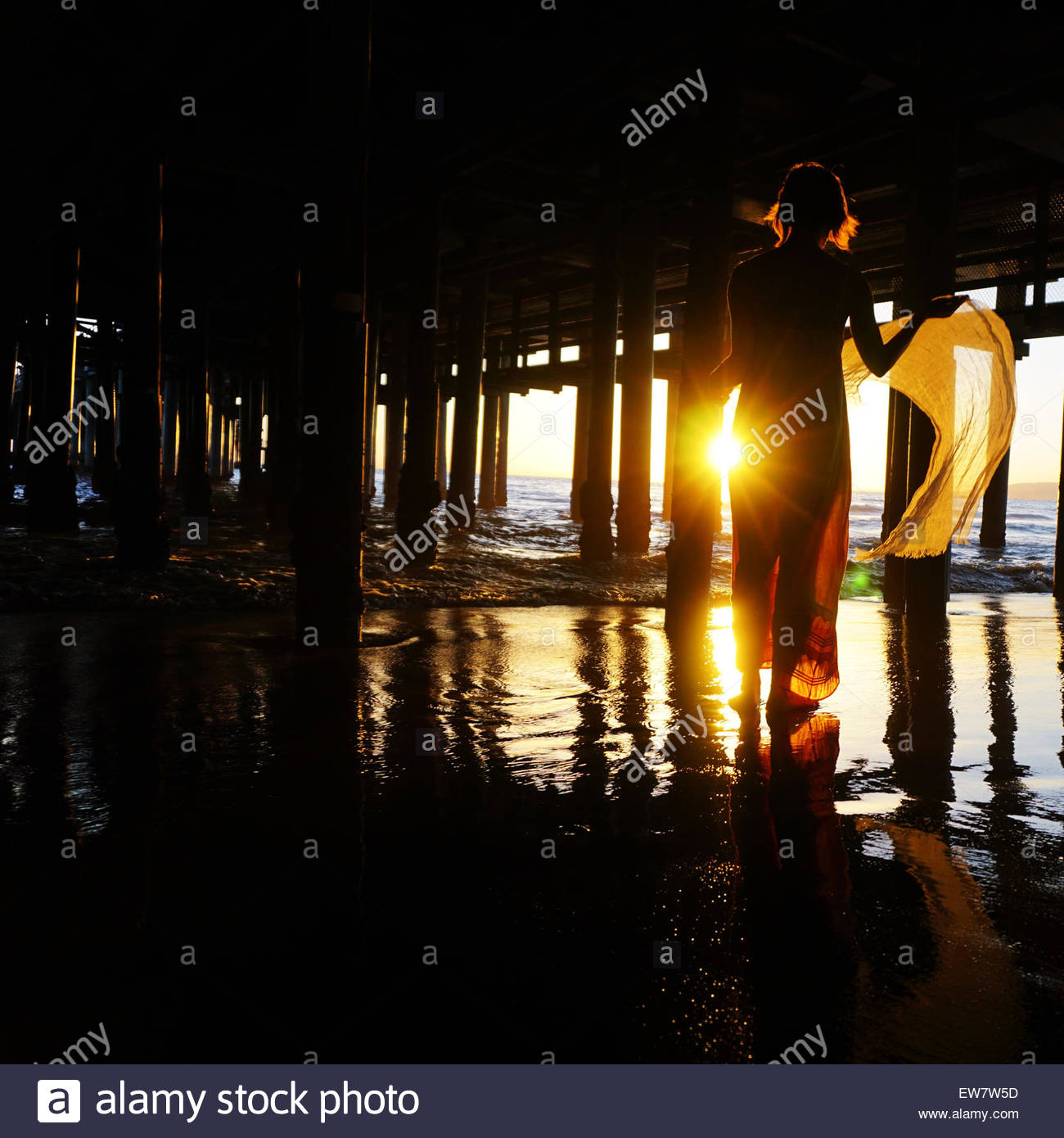Silhouette of a woman standing under a pier - Stock Image