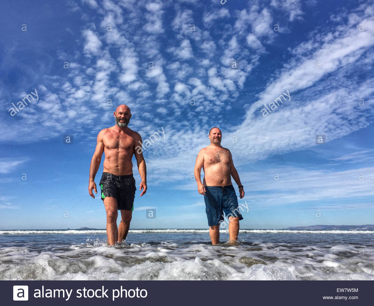 Two men walking out of the ocean, Ensenada, Mexico - Stock Image