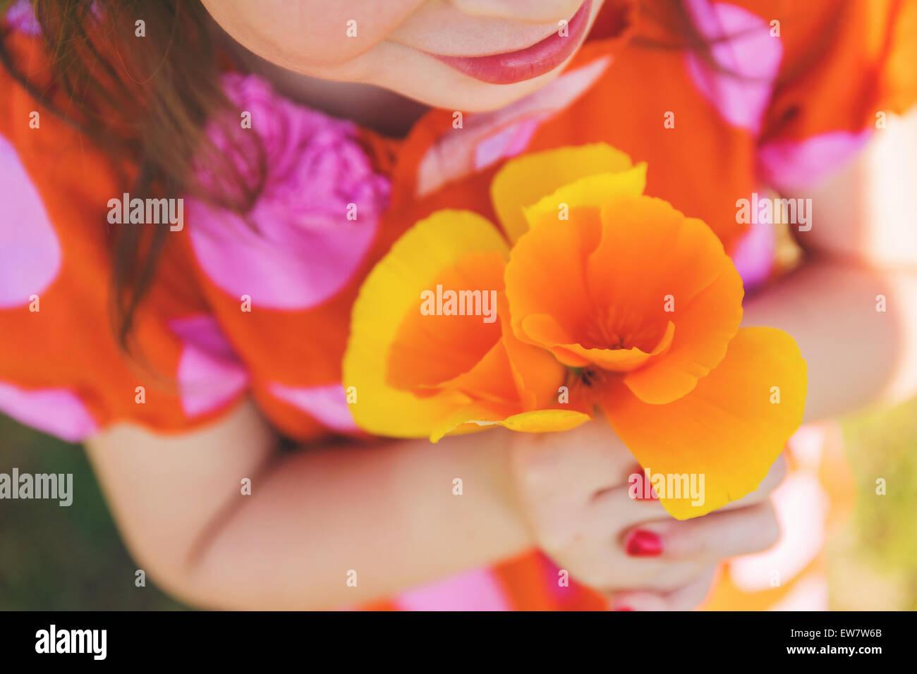 Close-up of a girl holding orange flowers - Stock Image