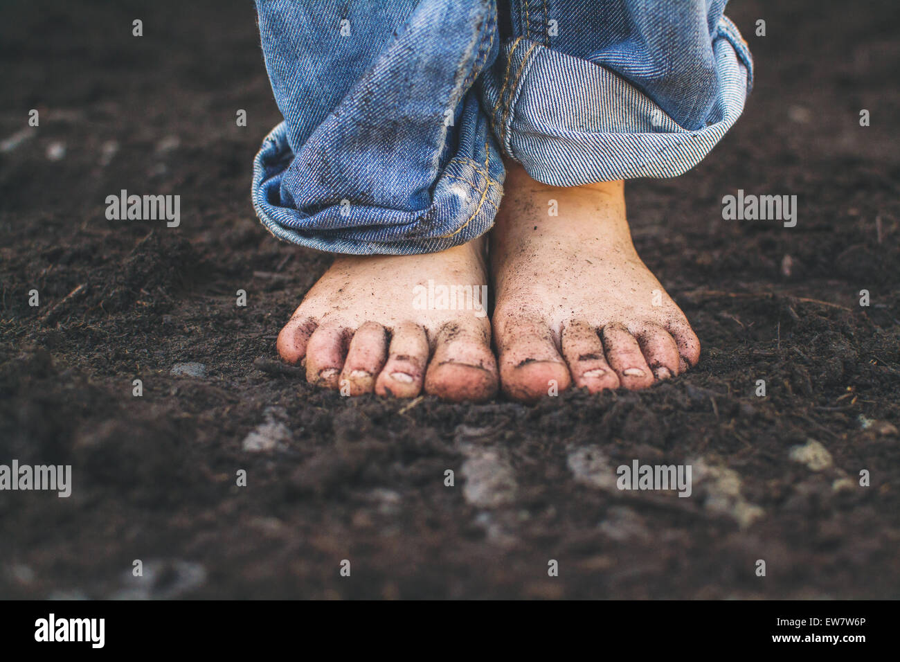 Close-up of a boy's dirty feet - Stock Image