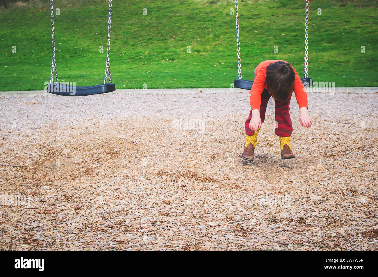 Boy hanging on a swing in a playground - Stock Image