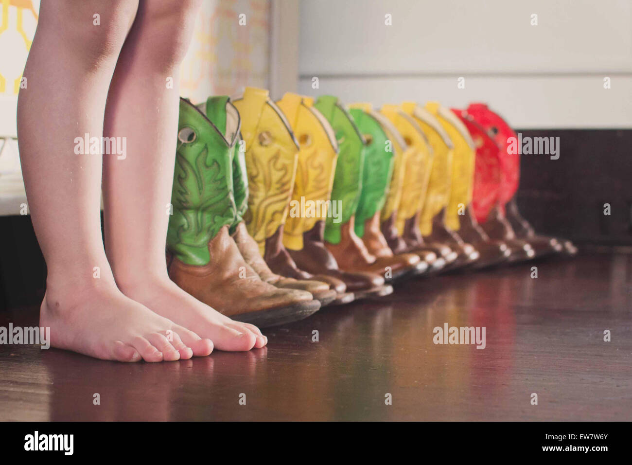Boy standing next to a row of colorful cowboy boots - Stock Image