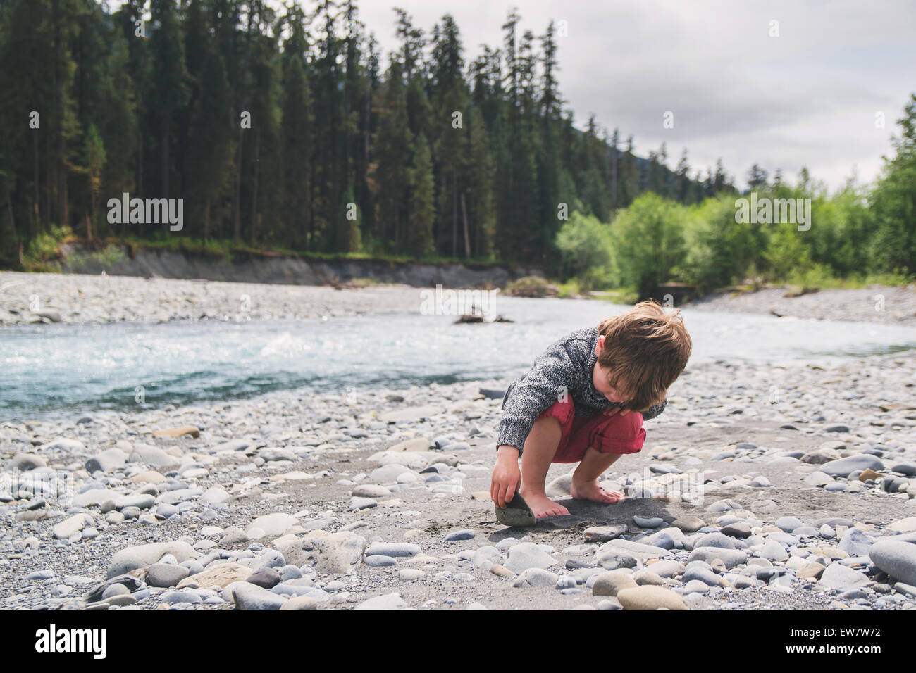 Boy looking under a rock in a river bed Stock Photo