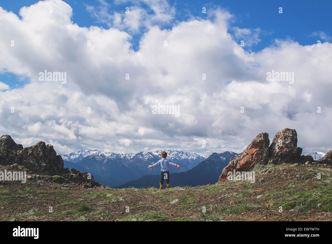 Boy standing on cliff on the top of a mountain - Stock Image