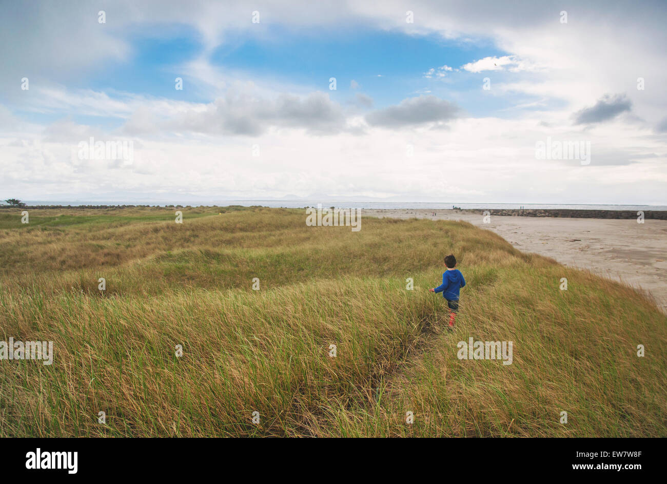 Boy running through grass on beach - Stock Image