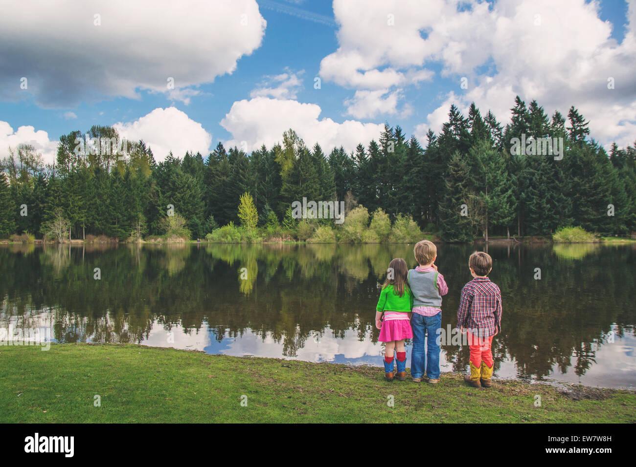 Three children looking at lake - Stock Image