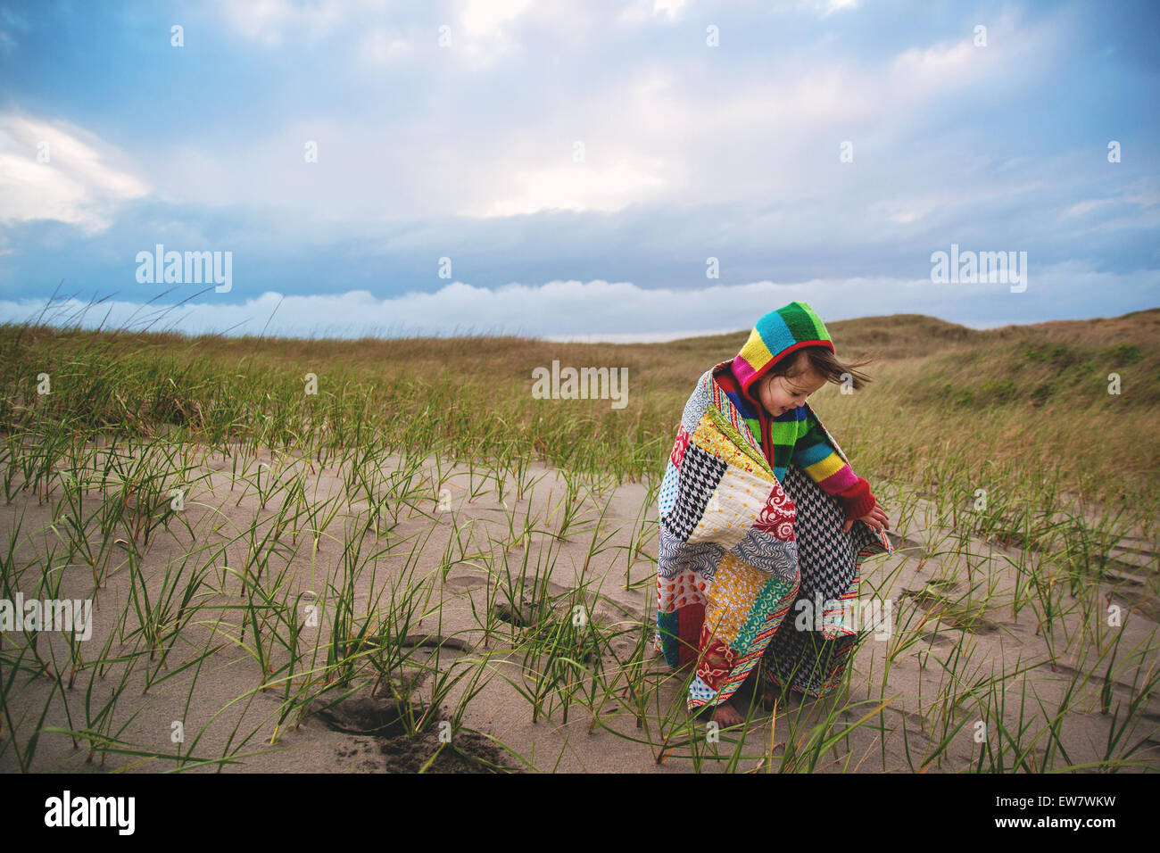 Girl on beach wrapped in a blanket - Stock Image