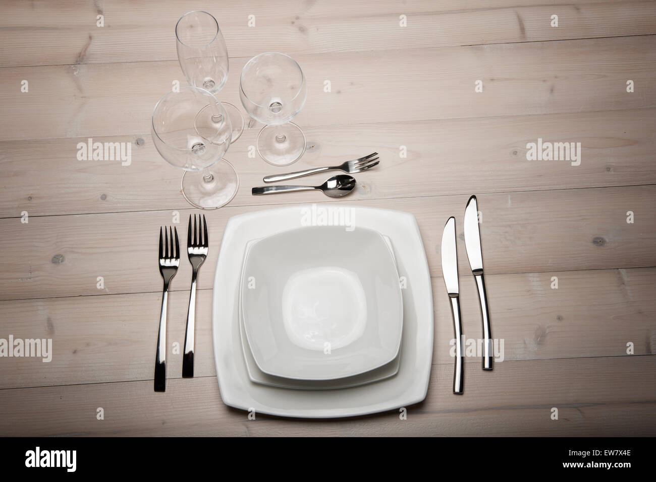 table set with plates, cutlery and glasses on wooden table - Stock Image