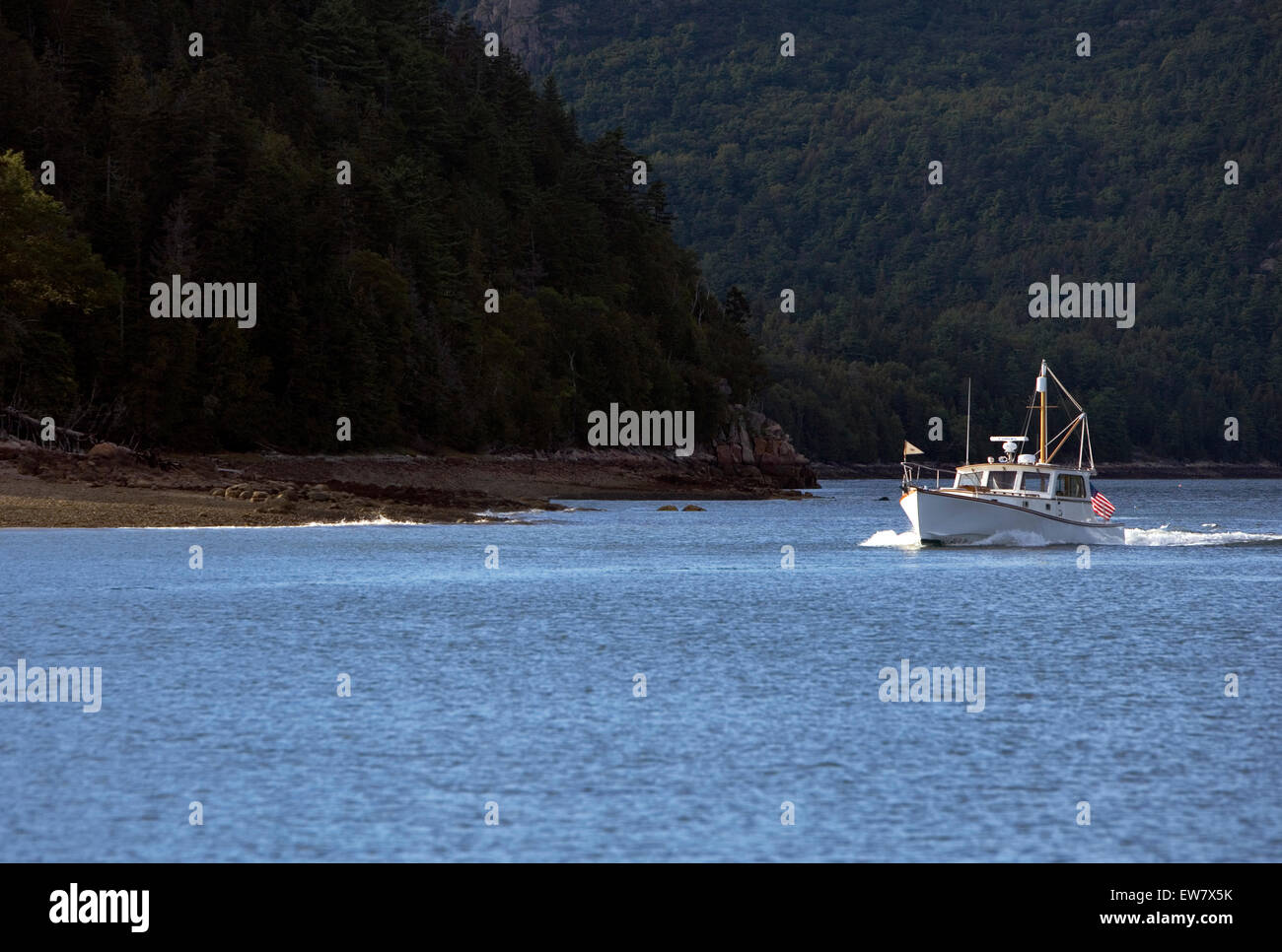 A classic fishing boat motors near the dark wooded shore. - Stock Image