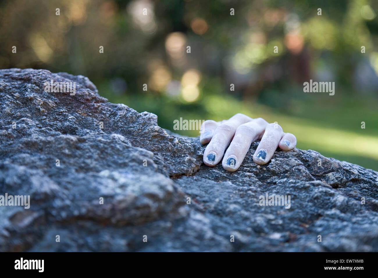 A climber's hand appears at the edge of a precipice during a bouldering session at Indian Rock in Berkeley, - Stock Image