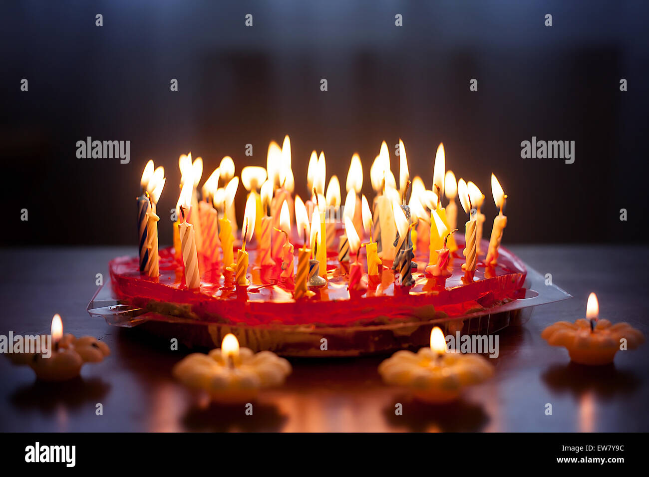 Strawberry cake with lots of candles on a table - Stock Image