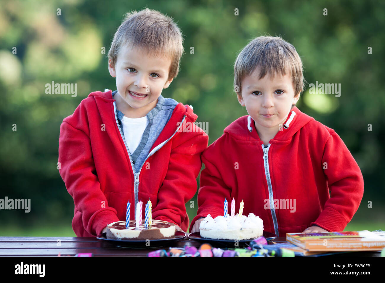 Two adorable boys with cakes, outdoor, celebrating birthday, having fun - Stock Image