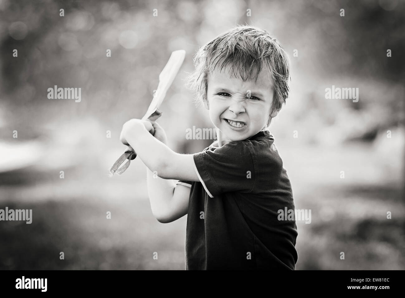 Angry little boy, holding sword, glaring with a mad face at the camera, outdoors in the park, monochrome conversion Stock Photo