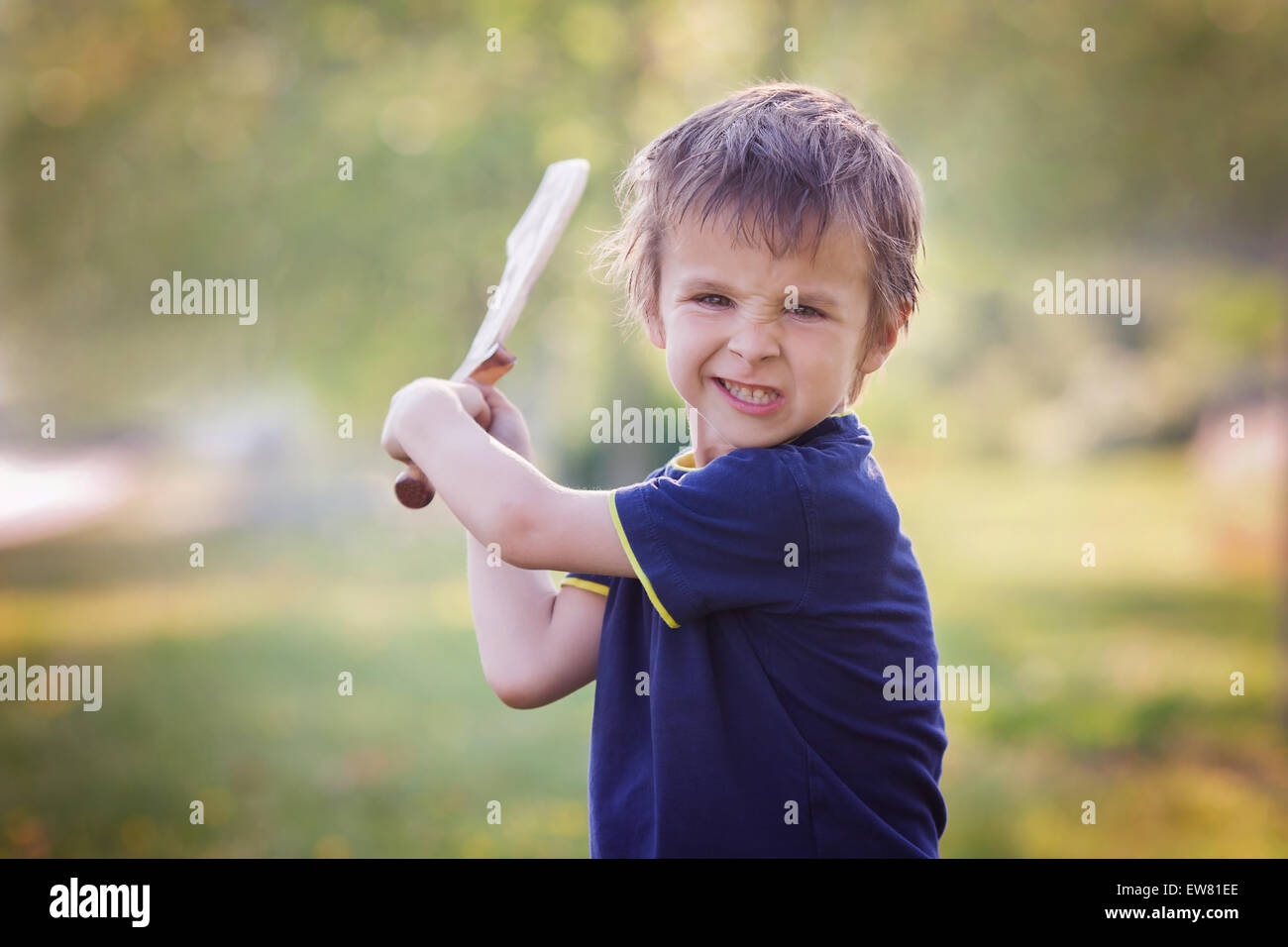 Angry little boy, holding sword, glaring with a mad face at the camera, outdoors in the park - Stock Image