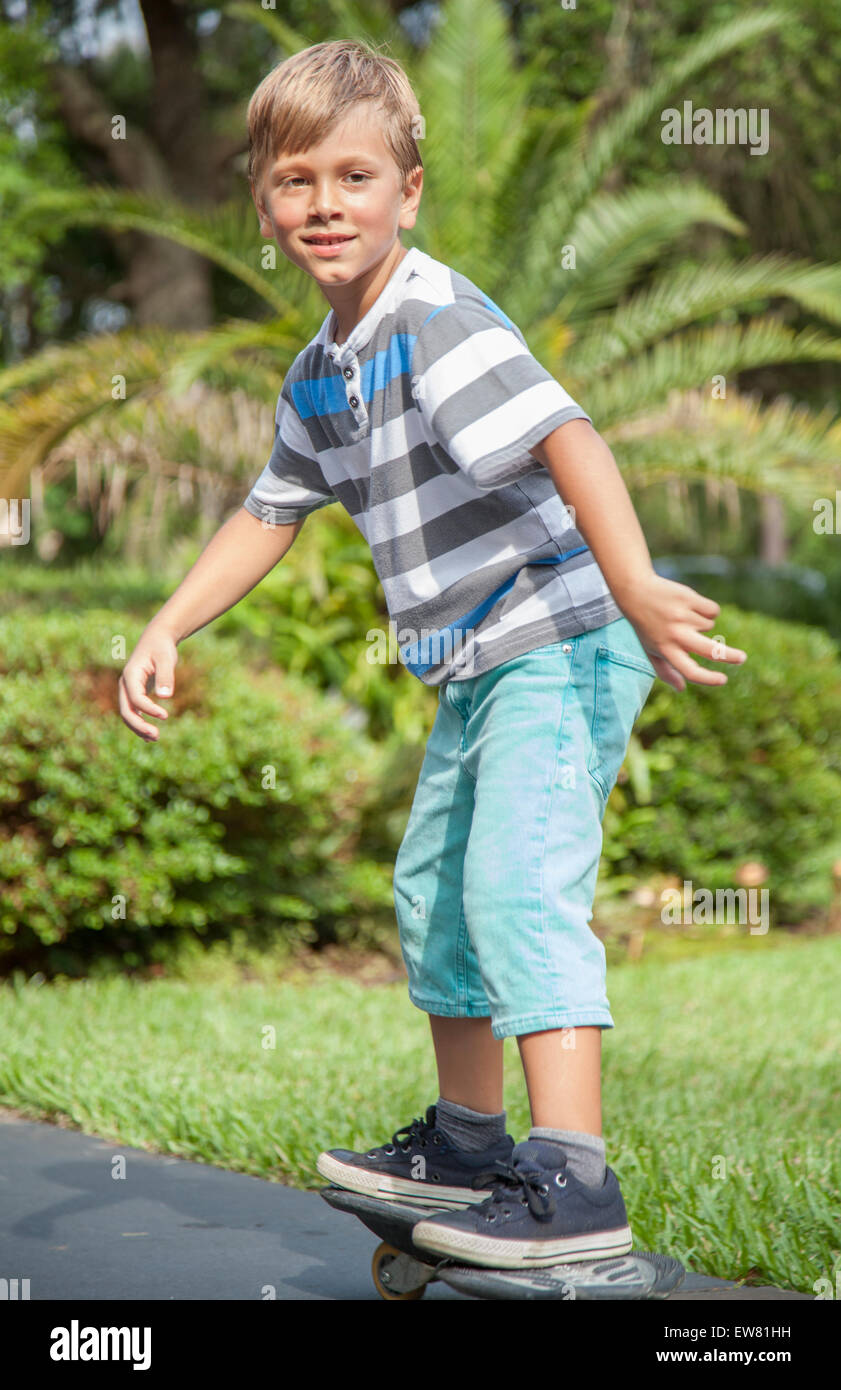Young blonde haired boy skateboarding in park - Stock Image