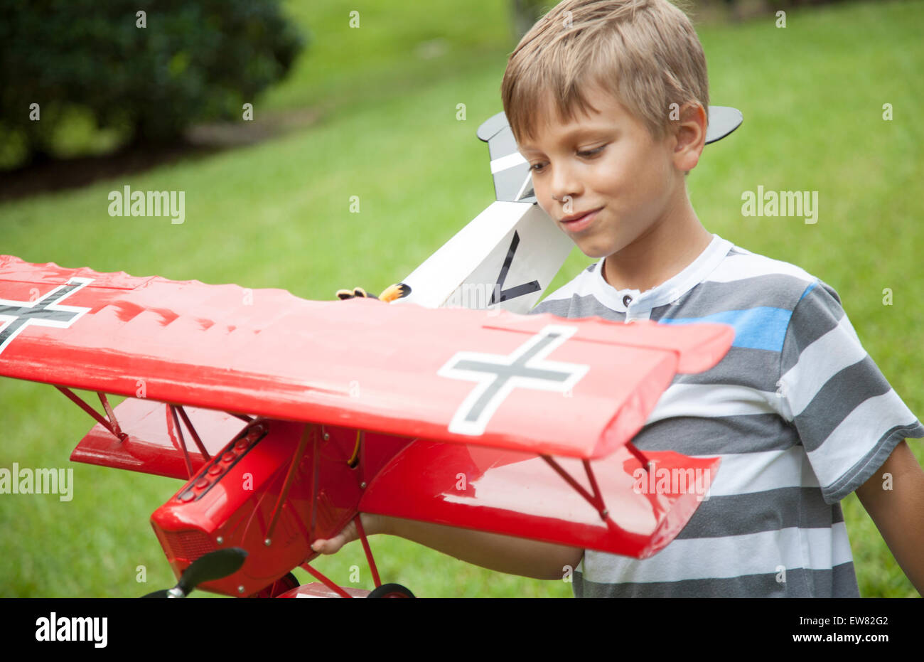 Young blonde haired boy playing with toy model red airplane - Stock Image