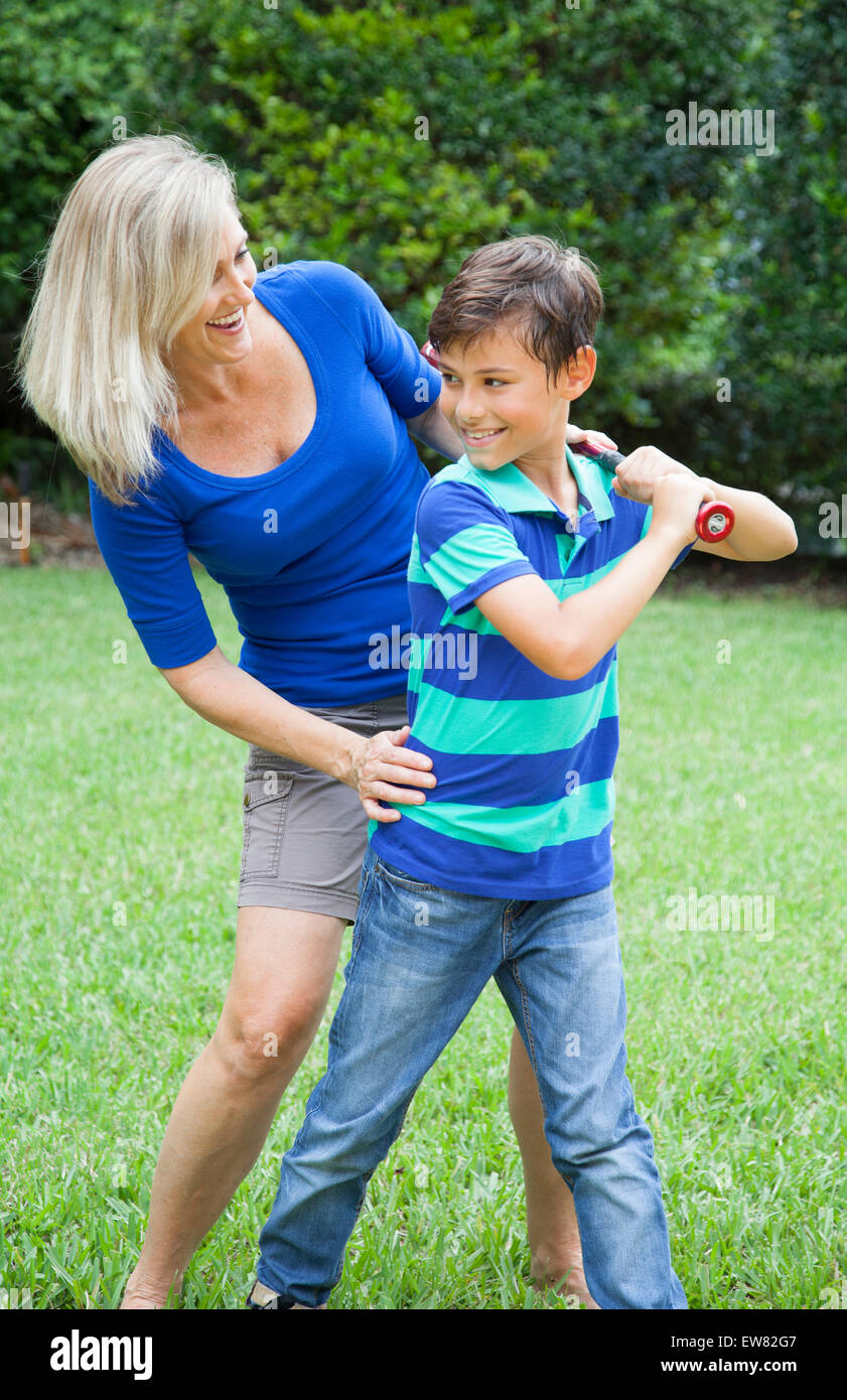 Mother and son playing baseball in yard Stock Photo