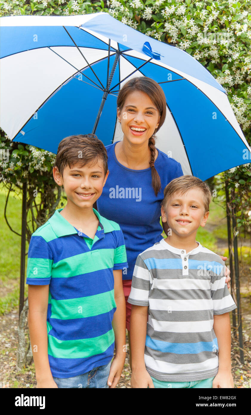 Single hispanic mother with two boys playing in the rain - Stock Image