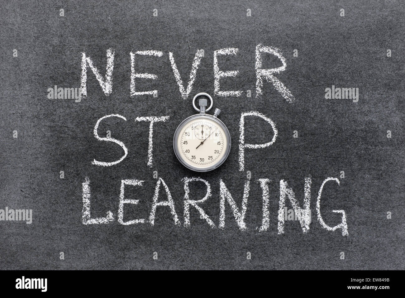 never stop learning phrase handwritten on chalkboard with vintage precise stopwatch used instead of O - Stock Image