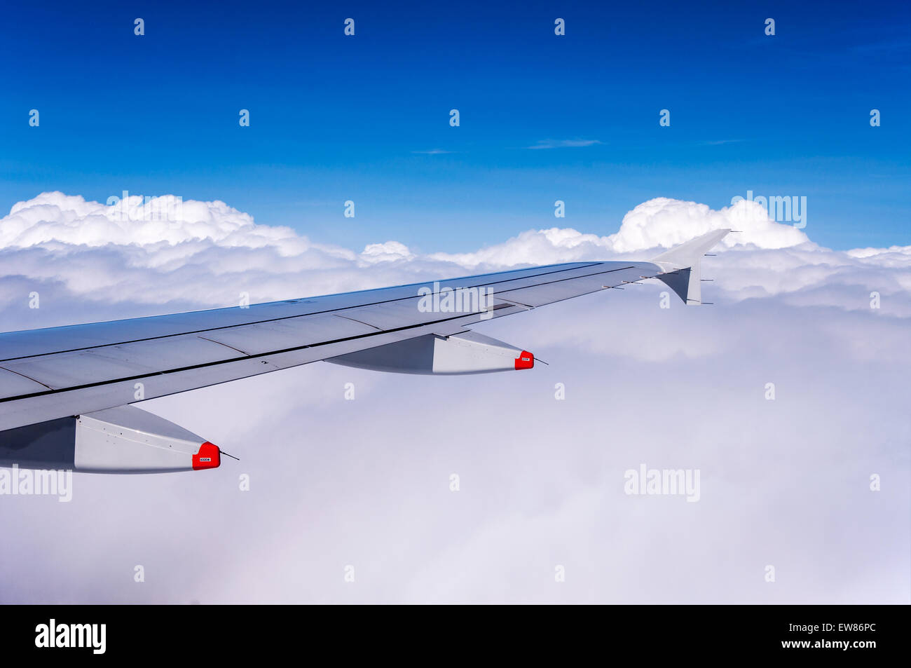 Aircraft wing over clouds with winglet and two anti-shock bodies serving also as flap track fairings - Stock Image