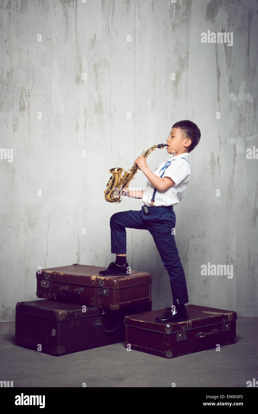 six years old boy stand on retro siuitcases and play sax - Stock Image