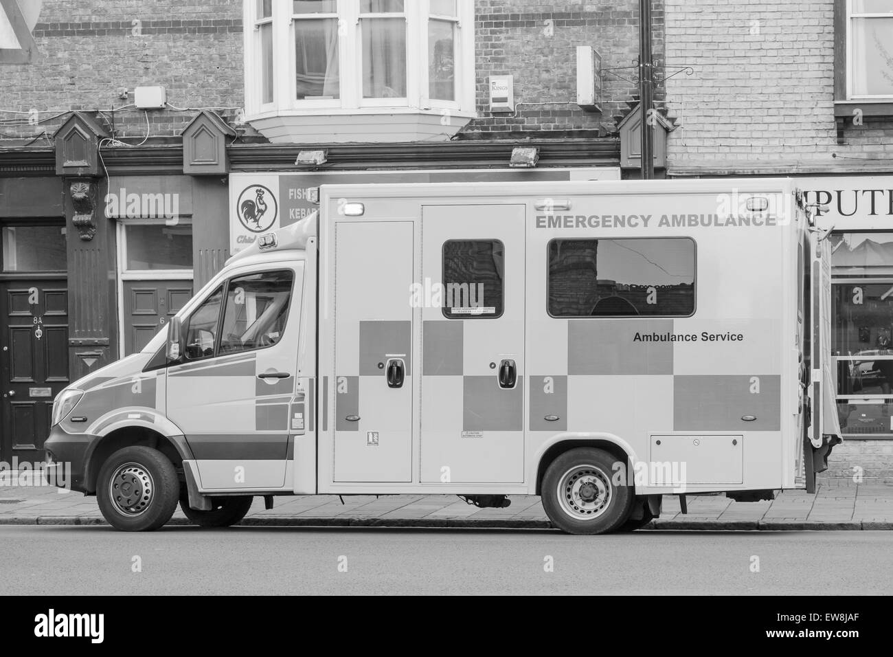 CAMBRIDGE, ENGLAND - 7 MAY 2015: NHS England Ambulance responding to an emergency on Mill road, Cambridge monochrome - Stock Image