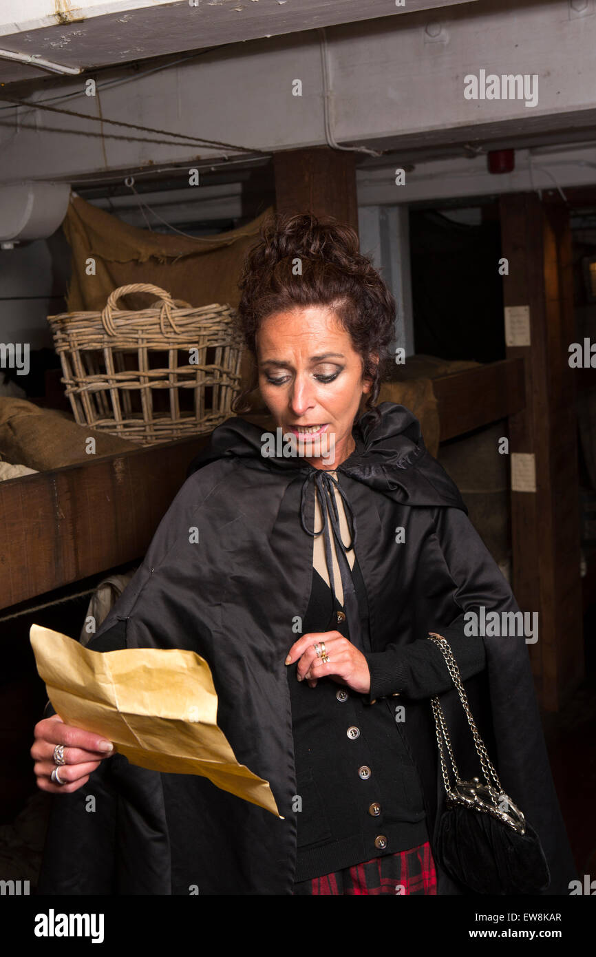 Ireland, Co Wexford, New Ross, First Class passage costumed character reading letter inside 1845 emigrant ship Dunbrody Stock Photo
